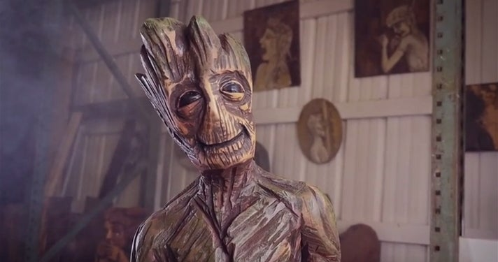 Woman carves groot statue out of wood with a chainsaw