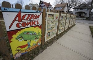 This Tuesday, April 2, 2013 photo shows oversized Superman comic book pages displayed on a fence outside of what was once Joe Shuster's boyhood home in Cleveland. Superman collaborators Jerry Siegel and Shuster lived several blocks apart in the Glenville neighborhood which shaped their lives, dreams for the future and their imagery of the Man of Steel. (AP Photo/Tony Dejak)