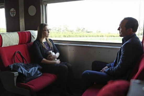 Simmons, wearing glasses, is seated on the left. Coulson is seated on on the right.  They are on a train and a window shows fields behind them.