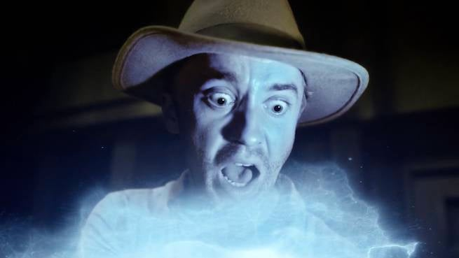 tom-felton-wearing-an-indiana-jones-fedora-while-screaming-at-a-savitar-box-like-in-raiders-of-the-lost-ark-on-the-flash