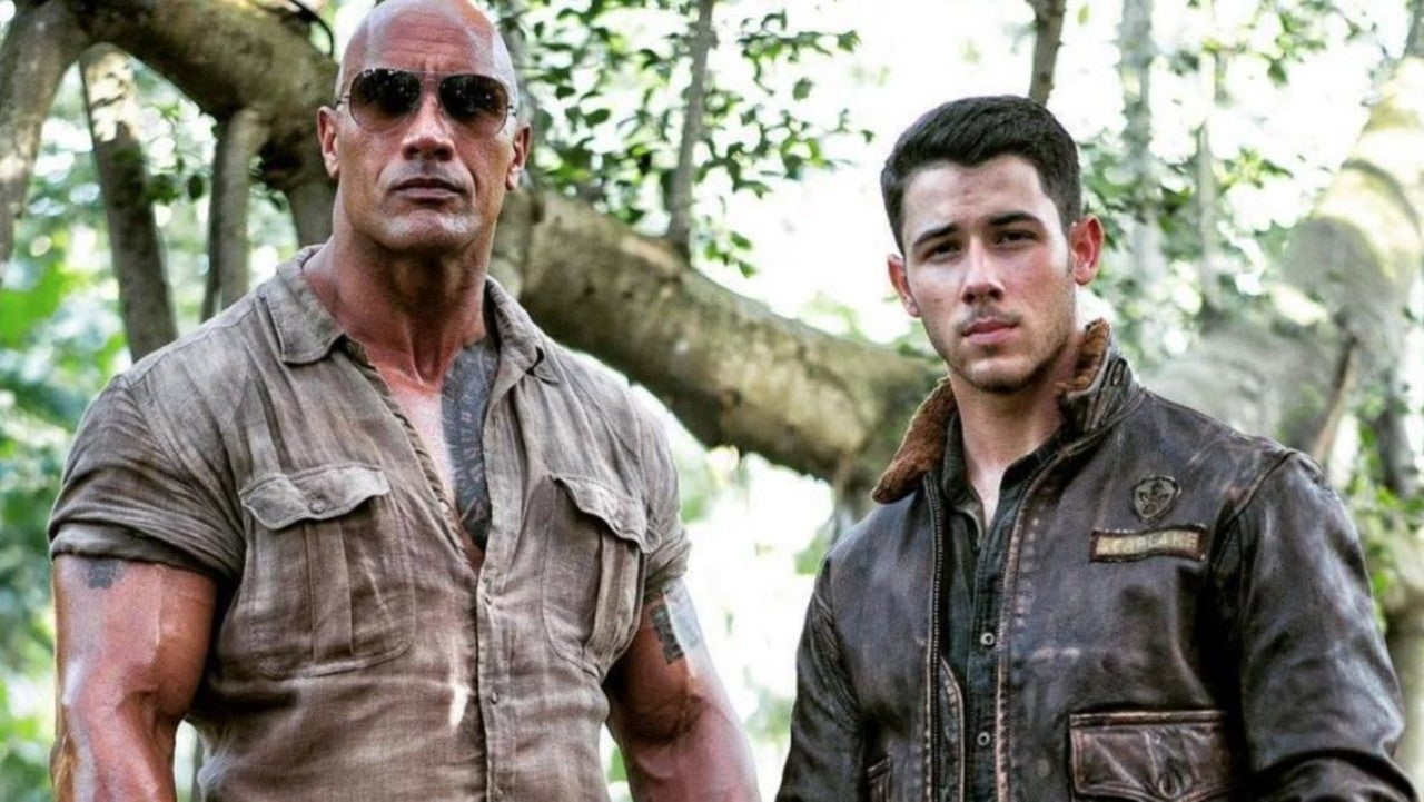 This Jumanji: The Next Level Holiday Video Shows Nick Jonas in the Director's Chair as the Cast Reluctantly Sings