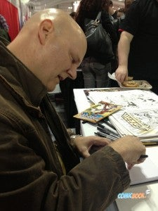 SAVAGE DRAGON creator Erik Larsen sketches for a fan at his table in Artists' Alley
