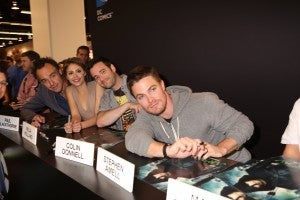 From left to right, ARROW stars Paul Blackthorne, Willa Holland, Colin Donnell and Stephen Amell pose for a fan photo at the show's signing session in the DC Entertainment booth at WonderCon on Sunday, March 31. ARROW airs Wednesdays at 8/7c on The CW. (©2013 Warner Bros. Entertainment, Inc. All Rights Reserved.)