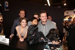 A young — and unmasked — Darth Vader greets the unhooded Arrow (Stephen Amell – right) at the show's fan signing in the DC Entertainment booth at WonderCon on Sunday, March 31. Also pictured are (left to right) series stars Paul Blackthorne, Willa Holland, Colin Donnell and executive producer Marc Guggenheim (back right). ARROW airs Wednesdays at 8/7c on The CW. (©2013 Warner Bros. Entertainment, Inc. All Rights Reserved.)