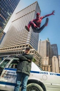 Amazing Spider-Man leaps through the air above a police car in a set photo