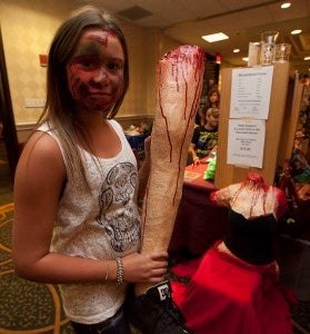 Hannah DuBois from Cherry Hill, N.J., shows off a leg made by her father, Brian Dubois, a special effects artist. Their stall has every body part you can imagine for sale, including a headless and limbless torso.